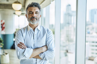 Confident businessman with arms crossed in office